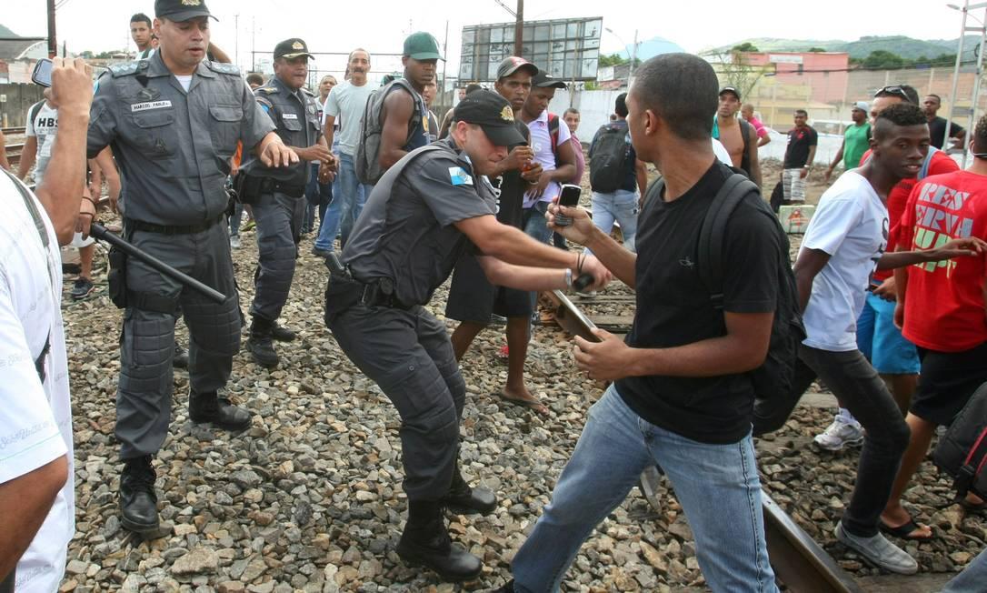 Com um cassetete, policial militar tenta retirar pasageiros da linha férrea em Oswaldo Cruz Foto: Guilherme Pinto / Extra