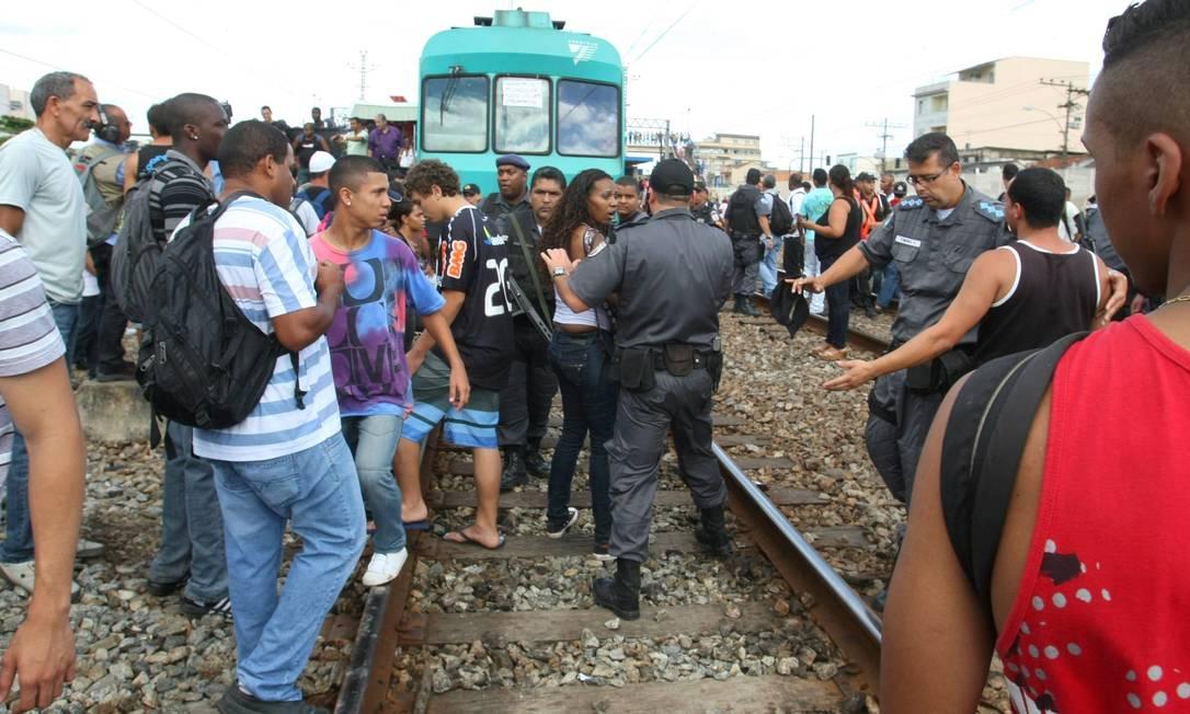 Policiais tentam retirar passageiros da linha férrea... Foto: Guilherme Pinto / Extra