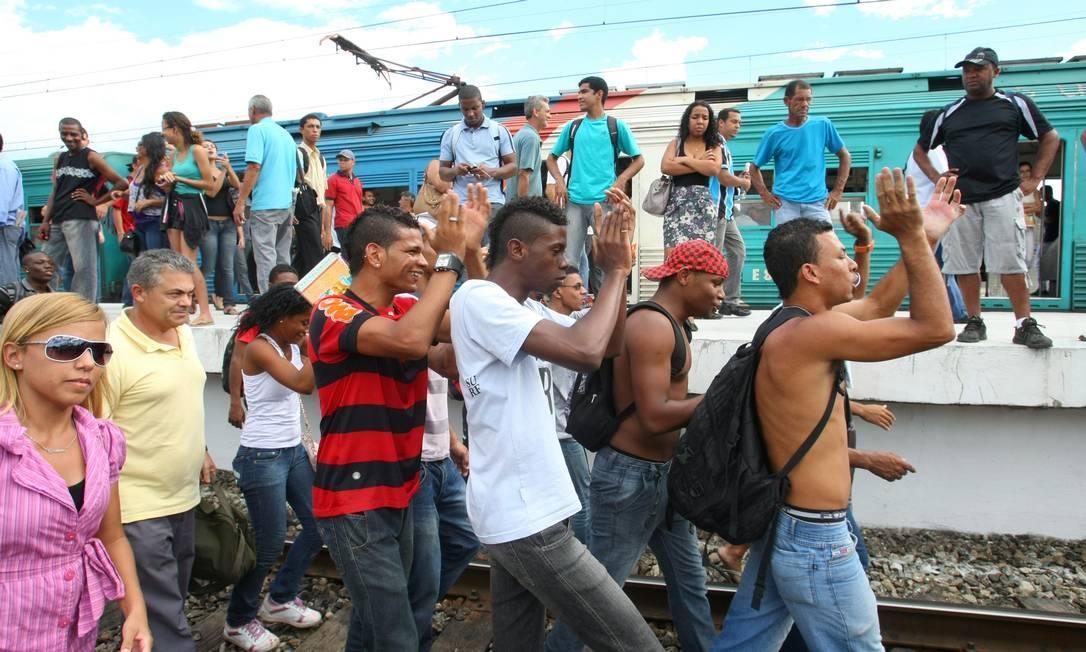 Passageiros precisaram caminhar pela linha férrea após a falha Foto: Guilherme Pinto / Extra