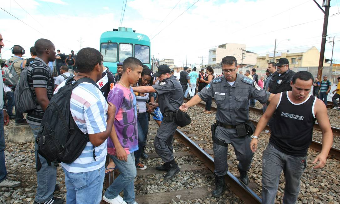 Policiais retiram passageiros da linha férrea Foto: Guilherme Pinto / Extra