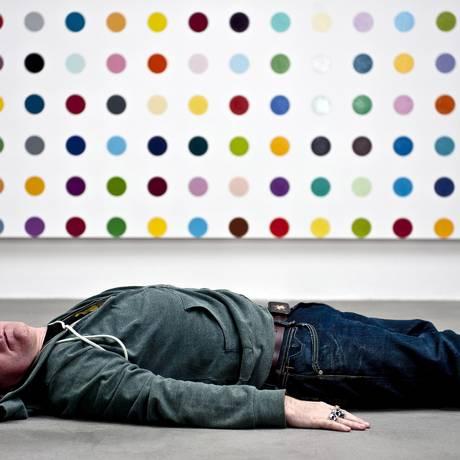 Damien Hirst posa ao lado de uma de suas controversas obras Foto: Andrew Testa/The New York Times