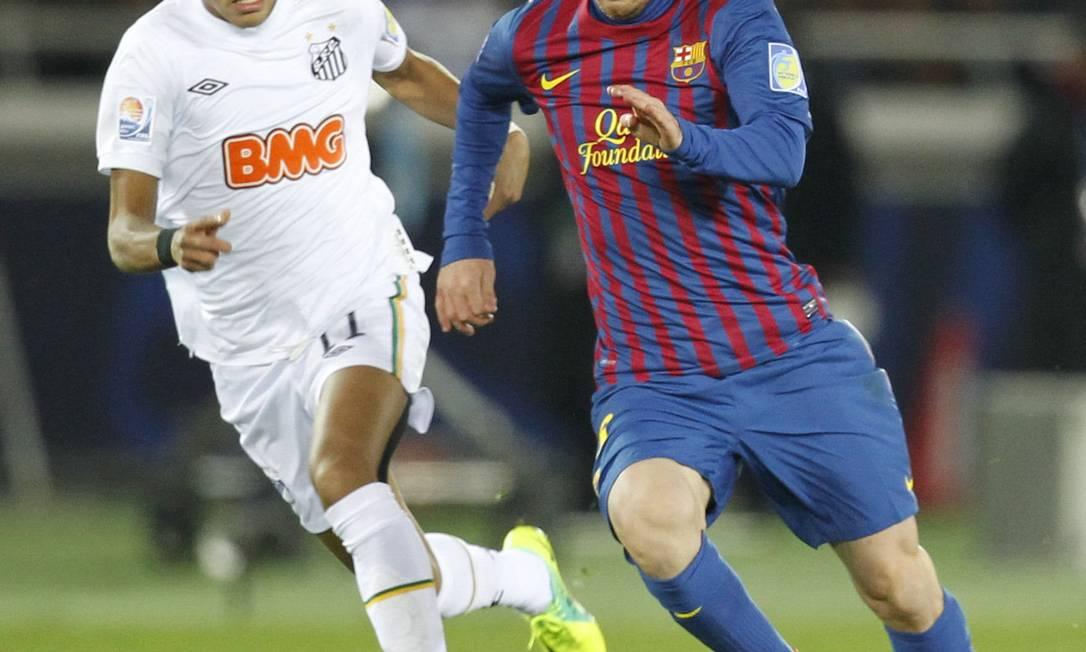 Messi domina a bola, acompanhado de perto por Neymar
