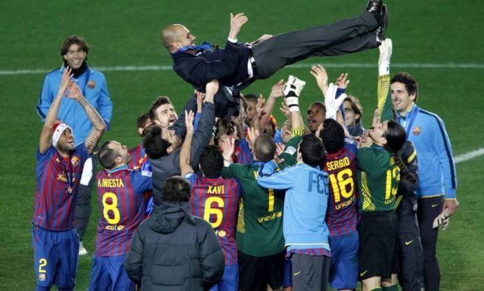 Jogadores do Barcelona jogam o técnico Guardiola para o alto Reuters