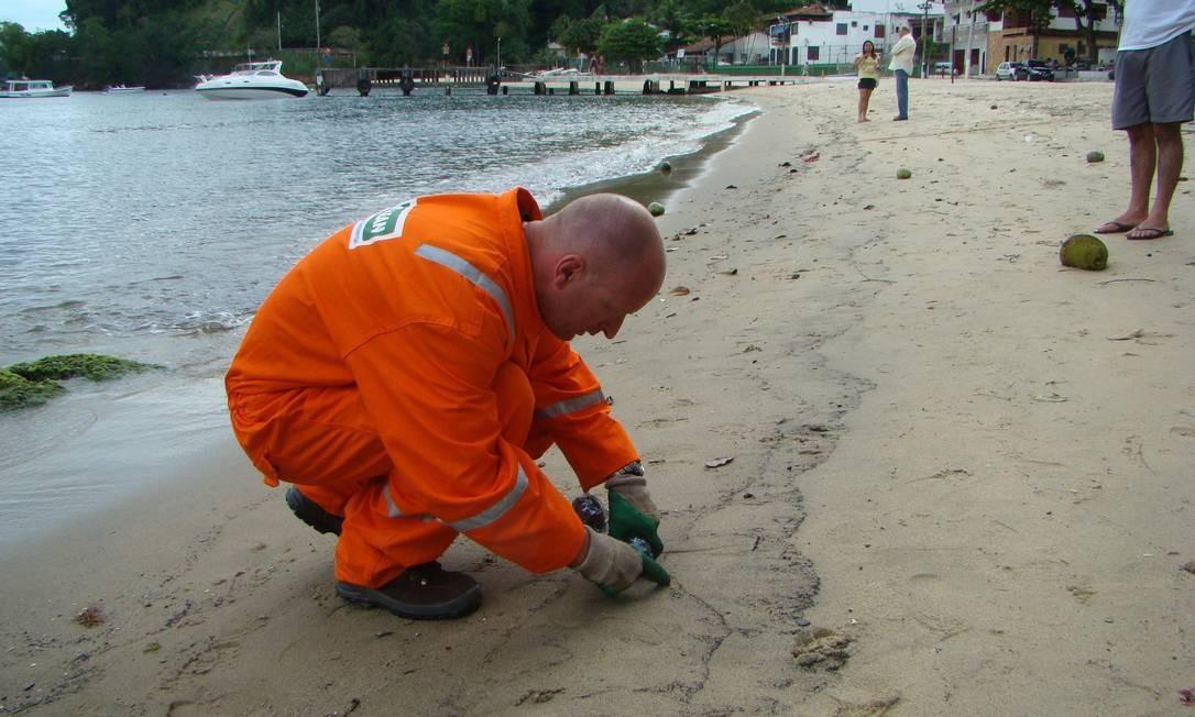 Técnico da empresa Hidroclean coleta amostras de areia com óleo na praia do Bonfim, em Angra dos Reis Foto: Agência O Globo / Paulo Roberto Araújo