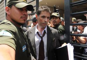 O juiz Walter Bento deixa a sede da Cablevisión protegido por policiais Foto: JUAN VARGAS / AFP