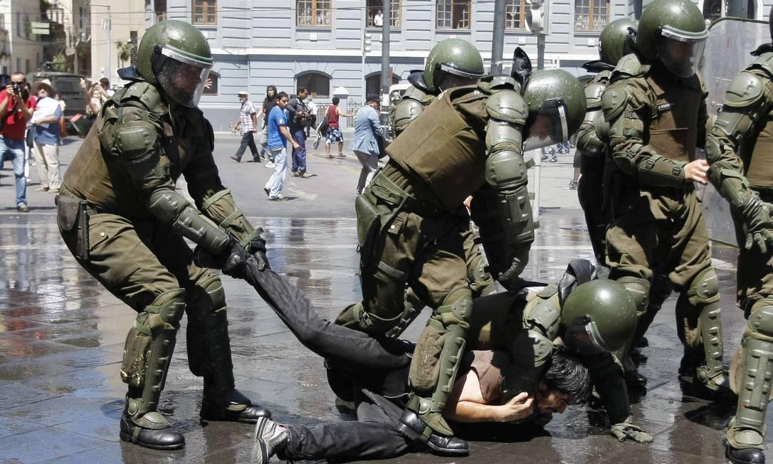 Jovem caído no chão é detido por grupo de policiais em Valparaíso Foto: Eliseo Fernandez / REUTERS