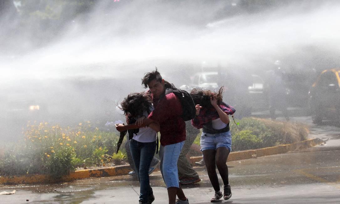 Manifestantes se protegem contra jatos de água usados pela polícia para reprimir protesto não autorizado na capital Foto: IVAN ALVARADO / REUTERS