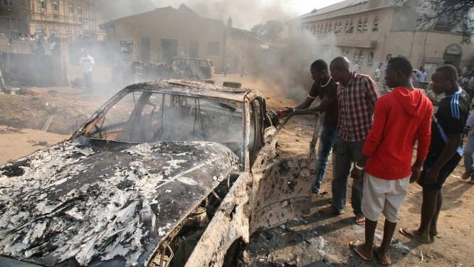 Pessoas observam carro atingido por bomba perto da igreja de Santa Teresa, em Abuja, capital nigeriana Foto: AFP
