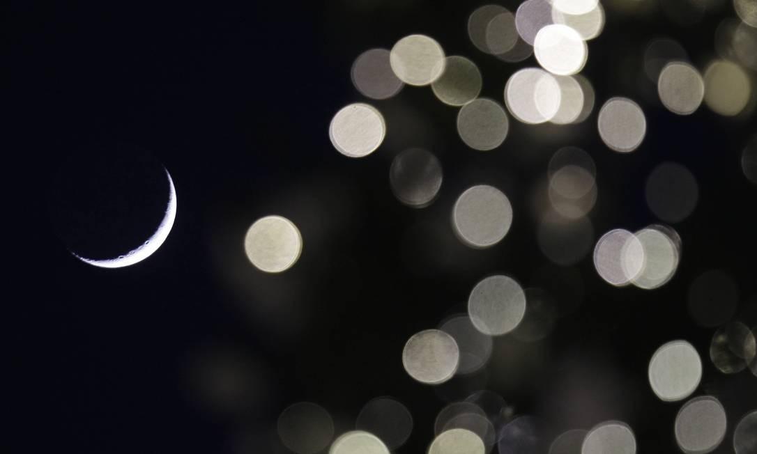 A Lua crescente vista entre a decoração de Natal em Milão, na Itália: novo calendário faria datas sempre caírem no mesmo dia da semana Foto: Luca Bruno / AP
