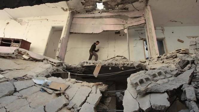 Um palestino caminha dentro de uma casa após um ataque israelense na Faixa de Gaza - Reuters