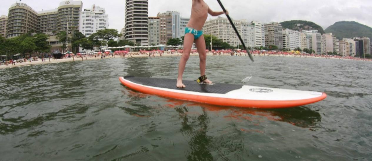 Lucas Lewis , de 8 anos, experimenta o stand up paddle no Posto 6 Foto: Marcelo Piu / O Globo
