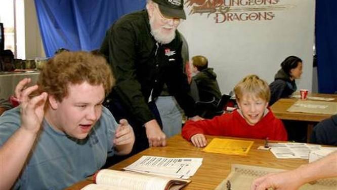Dois garotos jogando D&D ao lado de Dave Arneson, que criou o jogo em 1974 Foto: Andy King / AP Photo