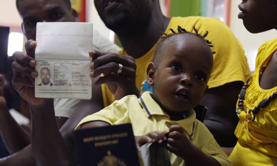Família de haitianos recebe seus documentos dentro de uma unidade de saúde do município onde todos são vacinados Foto: Michel Filho / O Globo