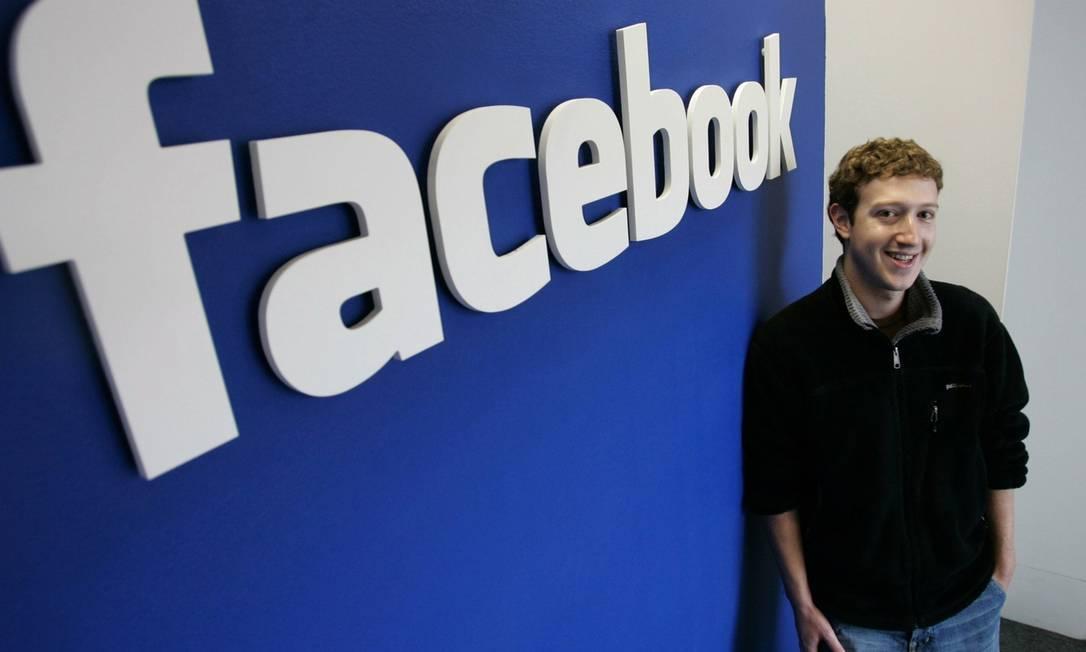 Mark Zuckerberg, criador do Facebook, posa ao lado de logomarca da empresa Foto: Divulgação
