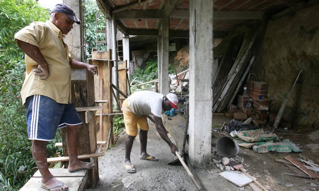 Davi observa operário trabalhando para reforçar estrutura do imóvel onde o filho mora, na comunidade da Garganta, em Santa Rosa Foto: Laura Marques