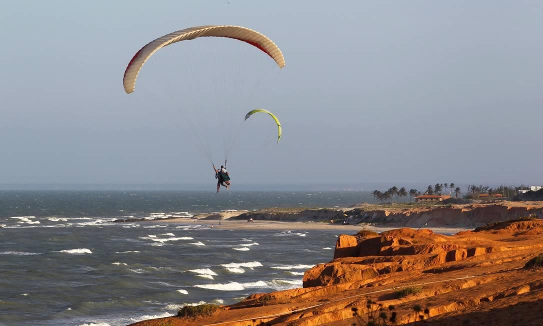 Devido ao vento forte e constante, o parapente parece flutuar sobre as falésias Foto: Custodio Coimbra / O Globo