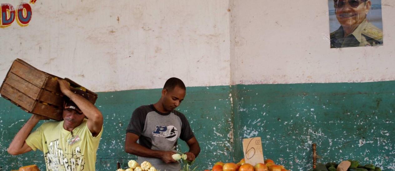 Mercado de frutas em Havana, com a imagem do presidente Raúl Castro ao fundo Foto: AP