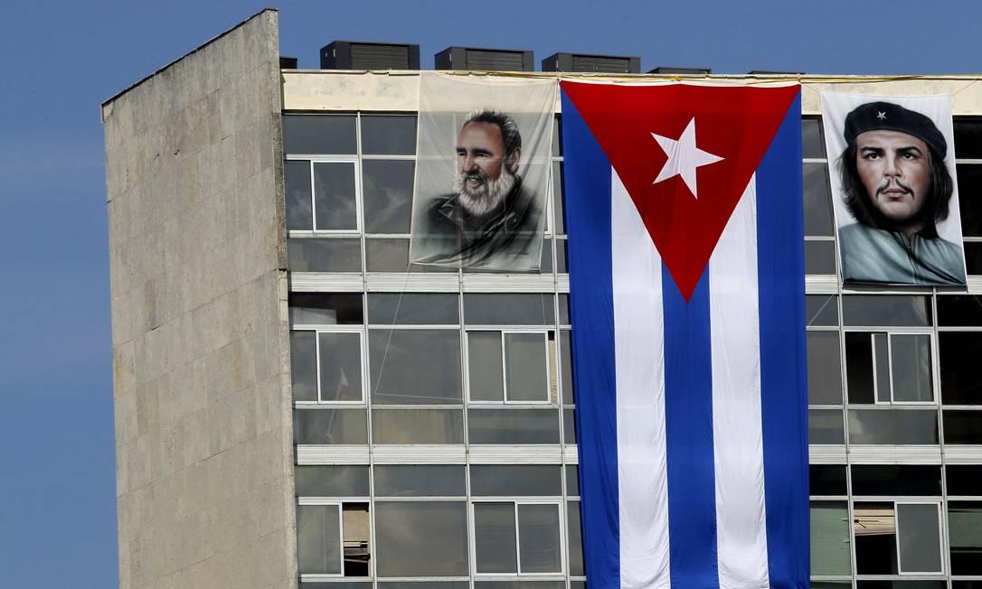 Bandeira cubana entre as imagens de Fidel Castro e Che Guevara em prédio de Havana Reuters
