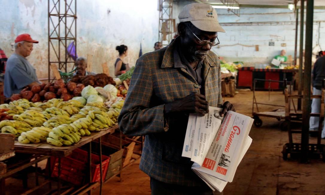 """Homem vende o jornal estatal """"Granma"""" num mercado da capital Reuters"""