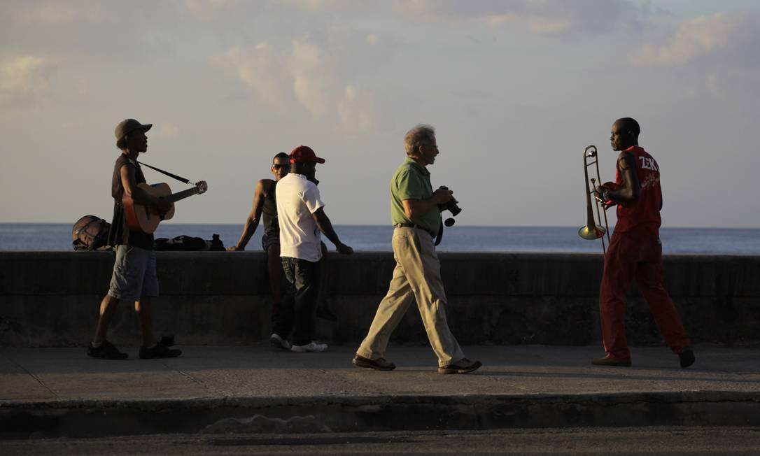 Turista caminha em praia de Havana em meio a músicos locais Reuters