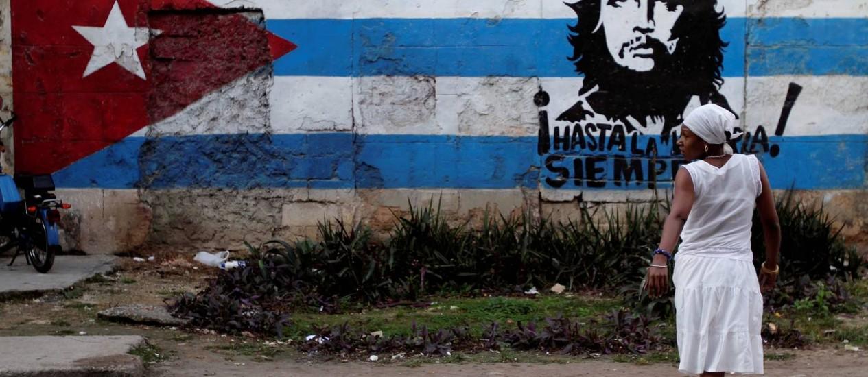 Em Havana, mulher caminha com a imagem de Che Guevara e da bandeira cubana ao fundo Foto: AP