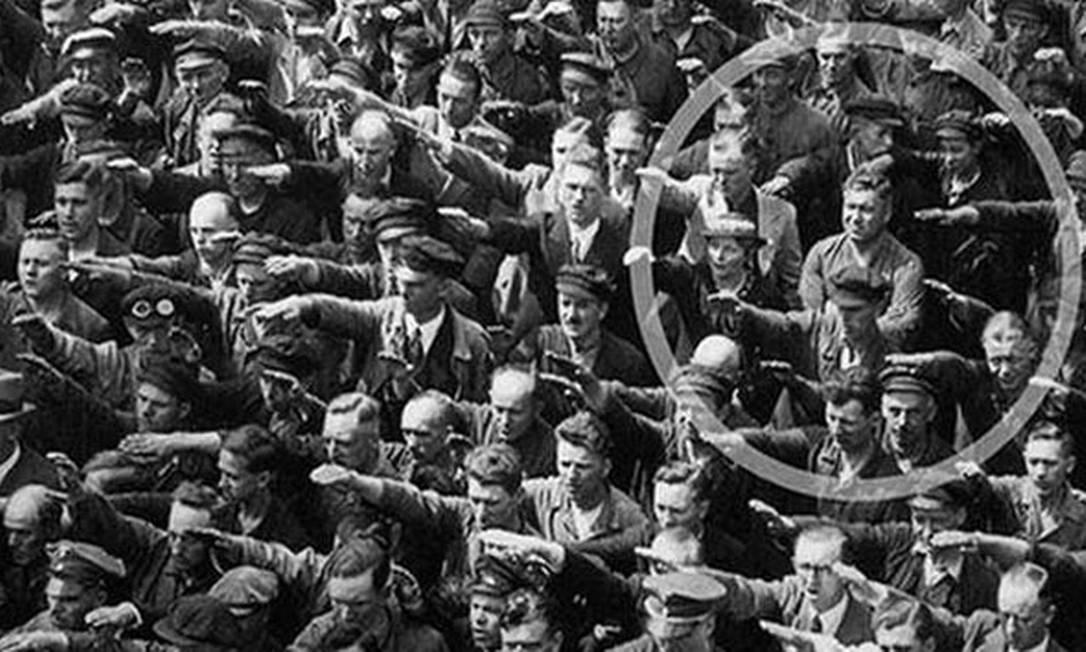 No destque, August Landmesser de braços cruzados durante saudação nazista Foto: Reprodução