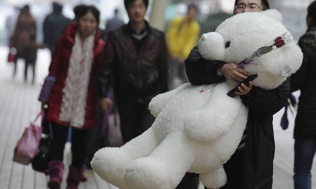Homem carrega rosa e urso de pelúcia em rua de Xangai AFP