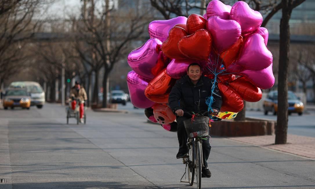Vendedor carrega dezenas de balões em formato de coração em Pequim. O governo da capital chinesa prevê que mais de quatro mil casais antecipem seus casamentos porque o Dia dos Namorados cai no ano lunar do Dragão em 2012 AFP
