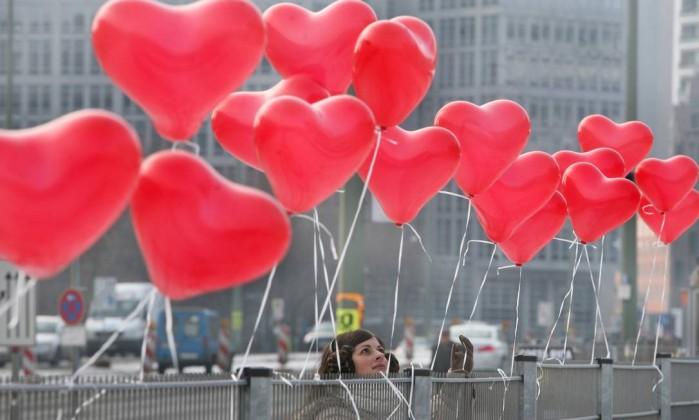 Mulher prende balão em grade de Berlim AFP