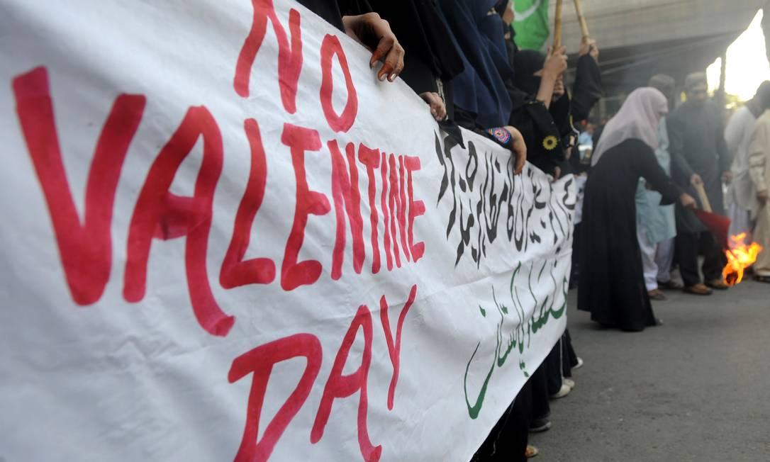 Mulheres paquistanesas do partido religioso jamiat-e-Ulama carregam cartazes e põe fogo em cartão durante protesto em Karachi. Alas conservadores do país reprovam a importação da tradição ocidental, que cresce ano a ano no Paquistão AFP