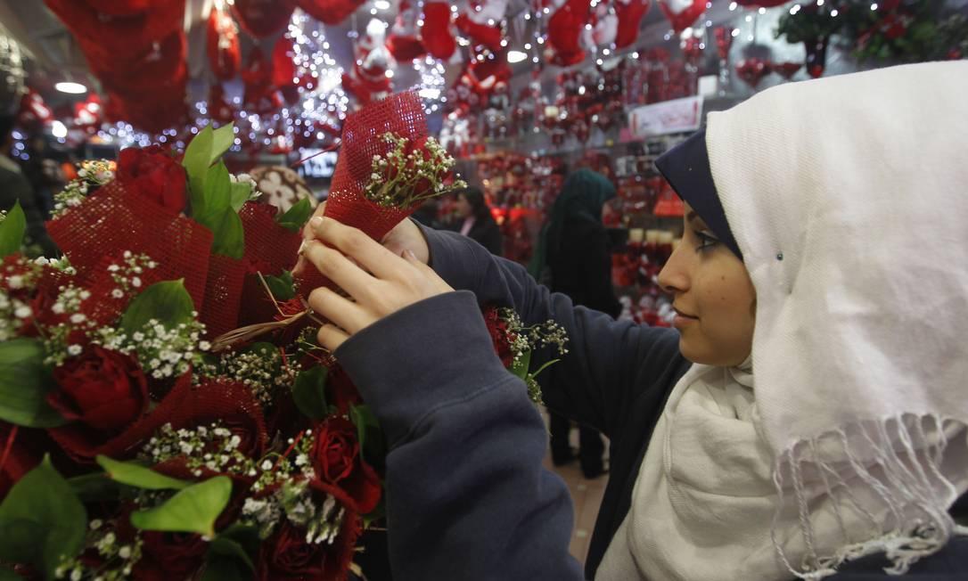 Mulher compra flores na Faixa de Gaza AFP