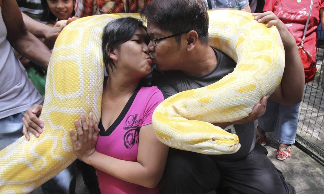 Casal se beija enquanto segura uma cobra de 200 kg durante apresentação no zoológico de Manila, nas Filipinas. REUTERS