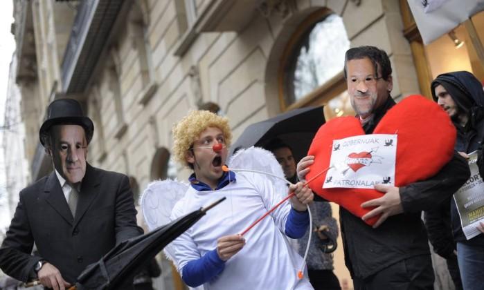 Em Bilbao, manifestante vestido de cupido acerta flecha no coração que representa o amor entre o governo e os negócios, segurado por um homem com máscara do primeiro-ministro Mariano Rajoy, ao lado de outro manifestante vestido como o presidente da Associação de Negócios Bascos, Miguel Angel Lujua Reuters