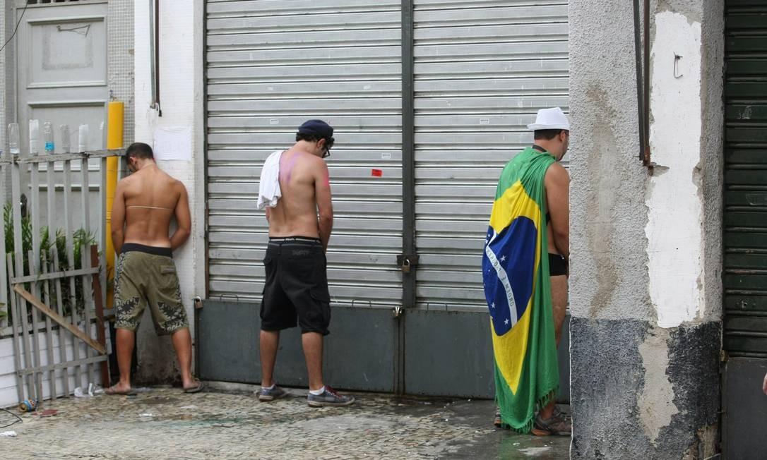 Rapazes usam as paredes como banheiro público, após a passagem do Toca Raul Foto: Eduardo Naddar/19-2-2012 / O Globo