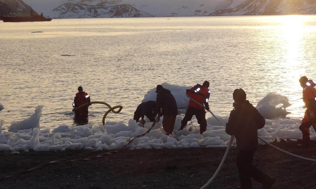 Militares usam mangueiras para puxar água do mar na tentativa de apagar o incêndio Reuters