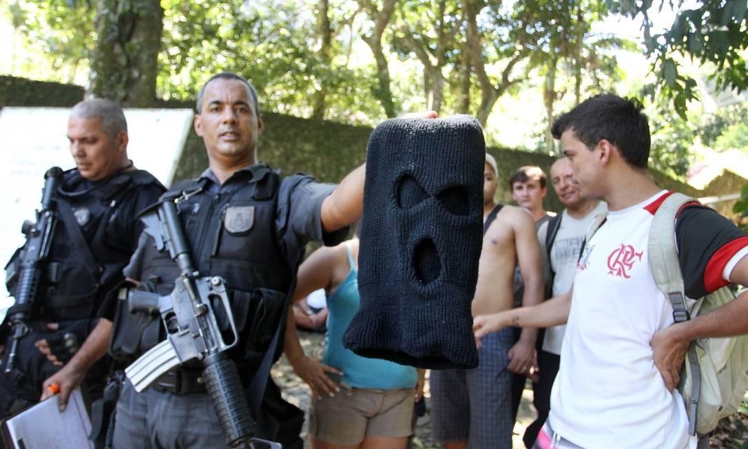 Policial mostra capuz usado por bandidos na Pedra da Gávea Foto: Márcia Foletto / O Globo