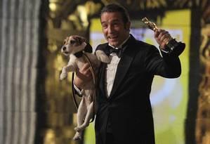 O vencedor do Oscar de melhor ator, Jean Dujardin, segura o cachorro Uggie enquanto comemora a vitória de 'O artista' Foto: AFP