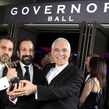 O diretor Asghar Farhadi entre o ator Peyman Maadi e o diretor de fotografia Mahmoud Kalari, na festa pós-Oscar Foto: LUCY NICHOLSON / REUTERS