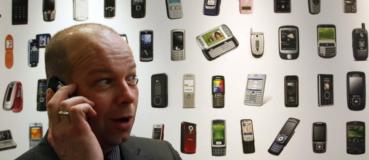Homem conversa no celular em frente a cartaz com vários modelos de aparelhos: segundo Proteste, com pesquisa carioca pode economizar quase R$ 4.000 Foto: Lluis Gene / AFP