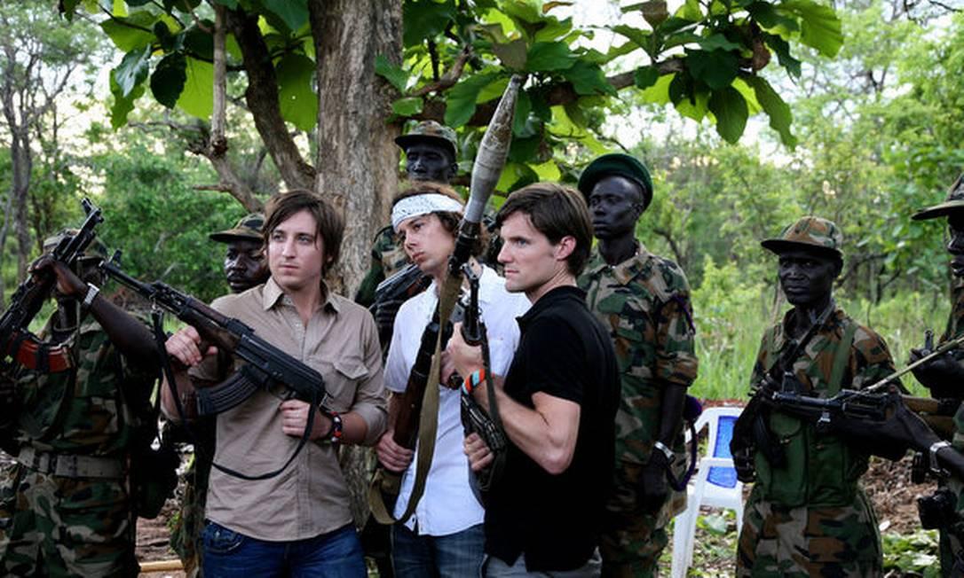 Os três americanos fundadores da ONG Invisible Children posaram, em 2008, segurando armas ao lado de soldados do Exército de Libertação do Povo Sudanês Foto: Reprodução