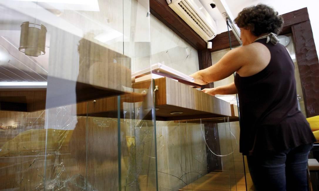 A dona de uma joalheria em Cabo Frio, Ester Magalhães, arruma a loja: a vitrine foi quebrada por ladrões Foto: Pablo Jacob / O Globo