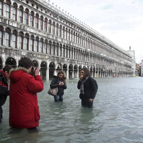 Turistas tiram fotos em áreas alagadas de Veneza Foto: Reuters/1-12-2008