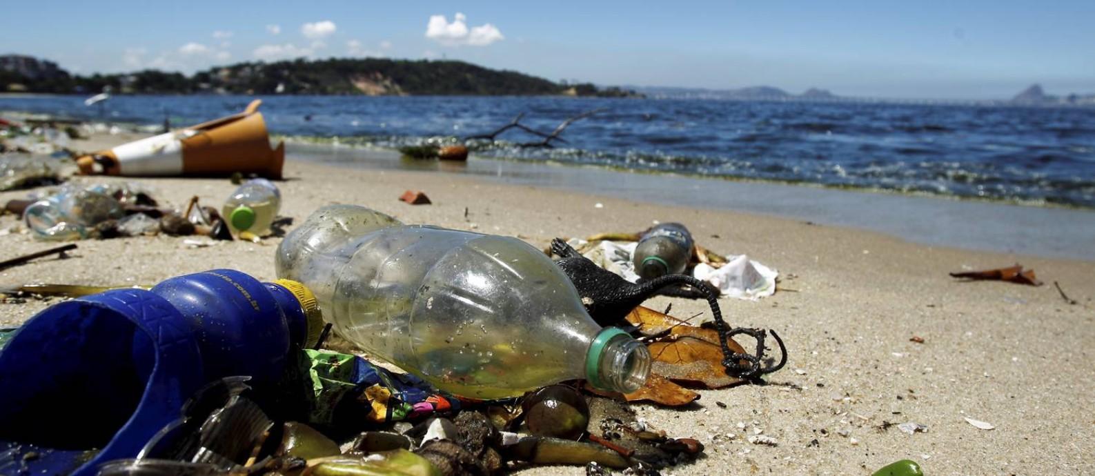 Garrafas sujam as areias da Praia da Bica, na Ilha do Governador: reciclagem de embalagens está no centro de uma polêmica nacional Foto: Marcelo Piu / O Globo