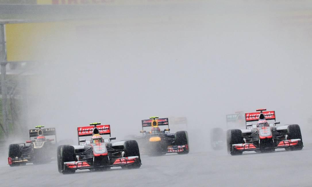 A largada do GP da Malásia, sob chuva forte, com as McLaren de Lewis Hamilton e Jenson Button na frente ROSLAN RAHMAN / AFP