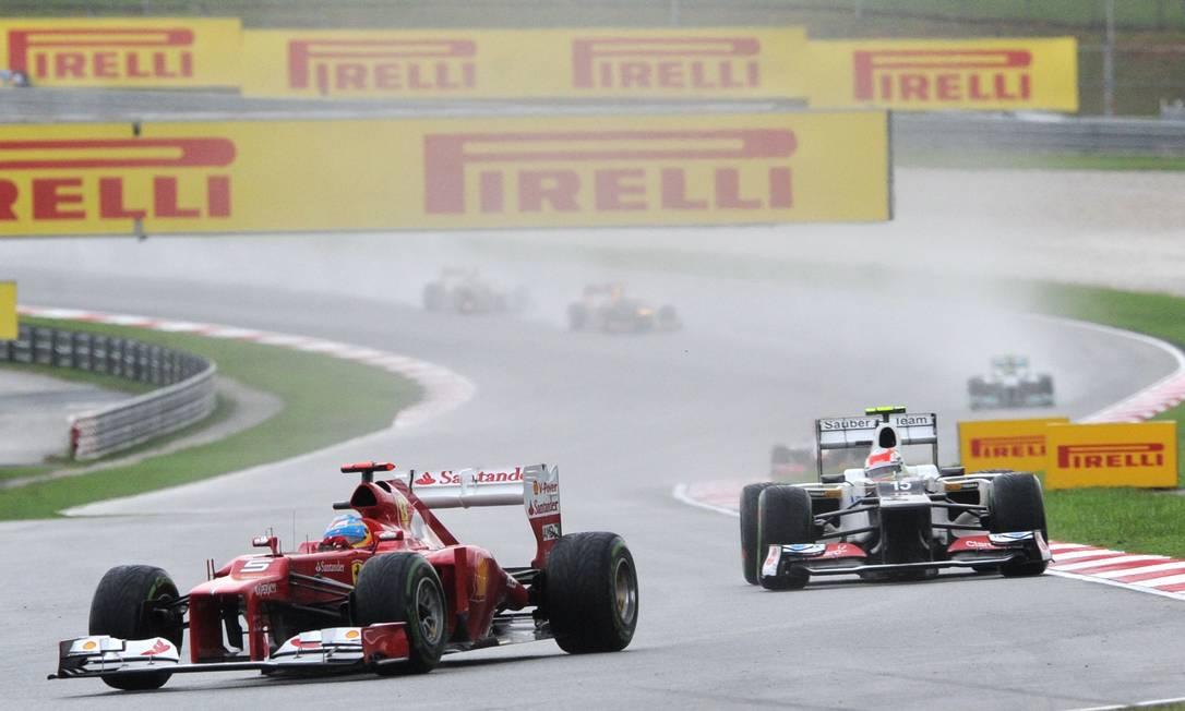 Fernando Alonso foi pressionado por Sergio Pérez no fim, mas conseguiu garantir a primeira colocação ROSLAN RAHMAN / AFP