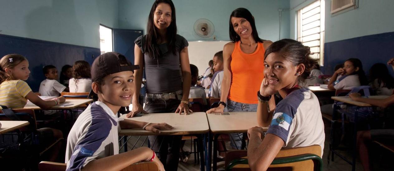 A professora Marcele Kloper (em pé, à esquerda) ao lado de Joelma de Lima, mãe de Felipe e Camila, alunos da rede pública em São Gonçalo Foto: Rafael Andrade / O Globo