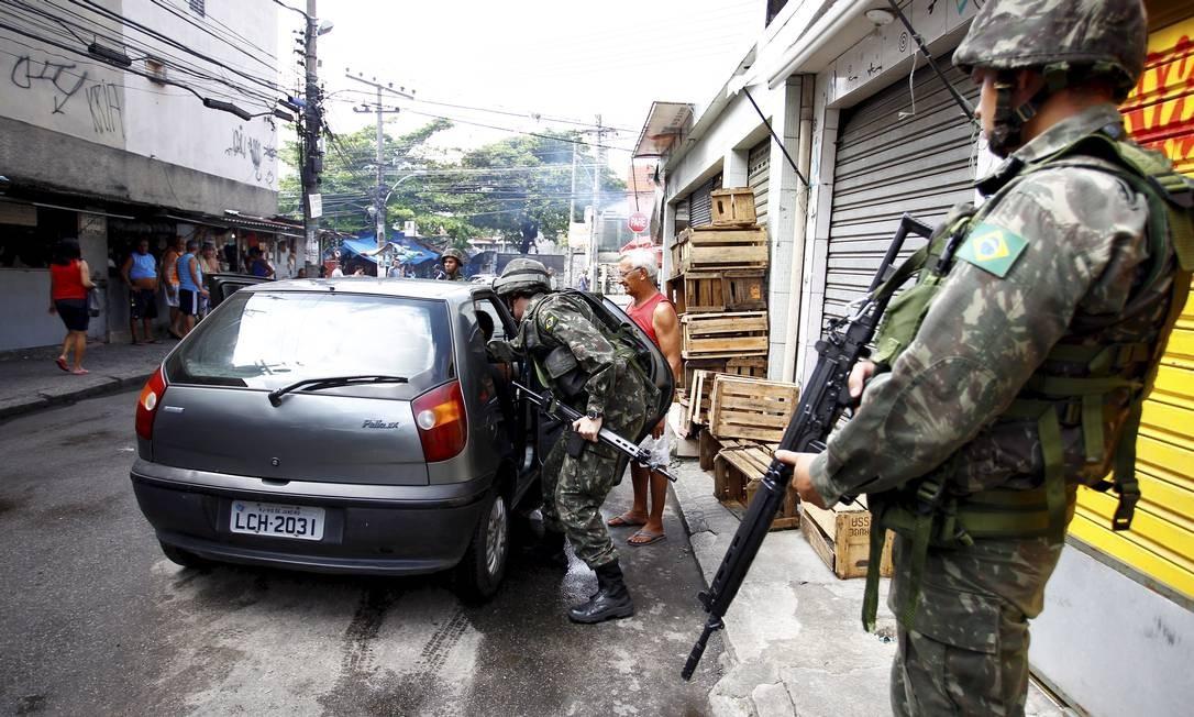 Militar da força de pacificação observa colega vistoriando um carro numa das entradas da Nova Brasília Foto: Pablo Jacob / O Globo