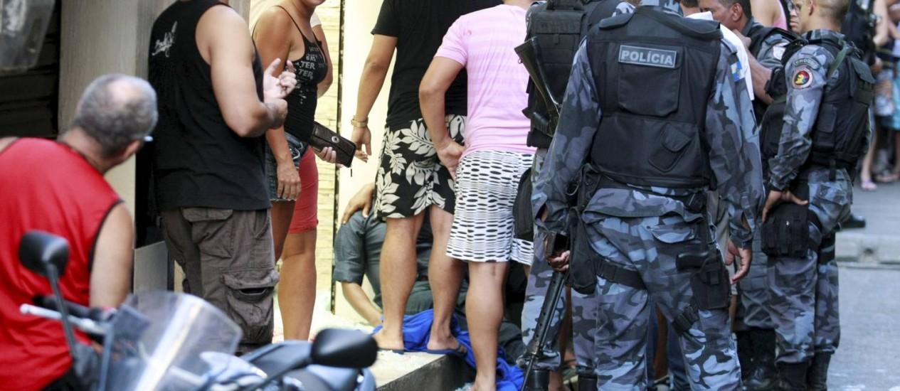 Policiais cercam o corpo do líder comunitário: este é sexto assassinato na favela após a pacificação Foto: Fabiano Rocha / Extra / O Globo
