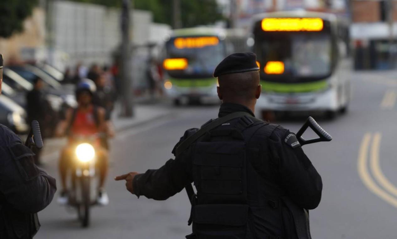 Na entrada do Complexo, um policial manda um motociclista estacionar Foto: Fernando Quevedo / O Globo