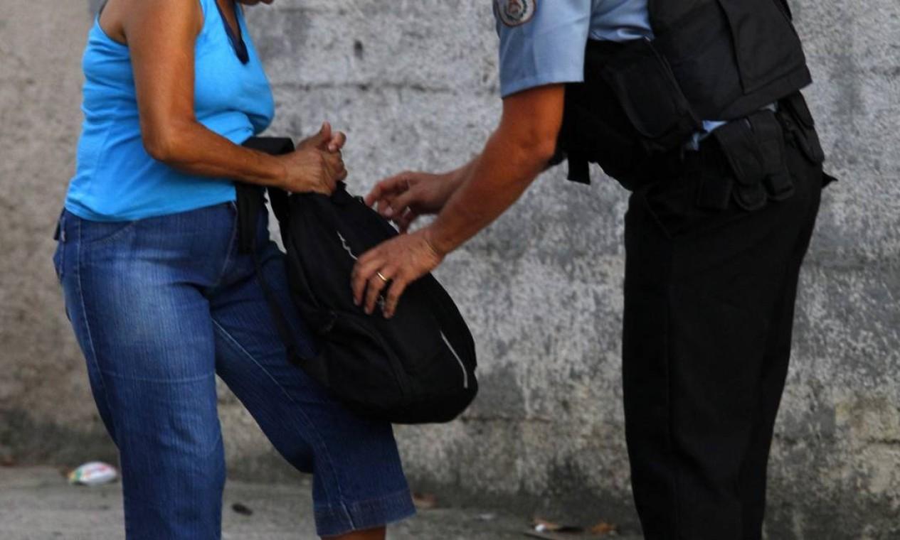 PM vasculha a mochila de uma moradora Foto: Fernando Quevedo / O Globo